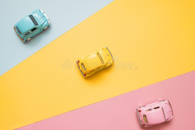 Small color toy cars on a yellow, pink and blue background. Business competition, winners and losers. Finish line. Small color toy cars on a yellow, pink and stock image