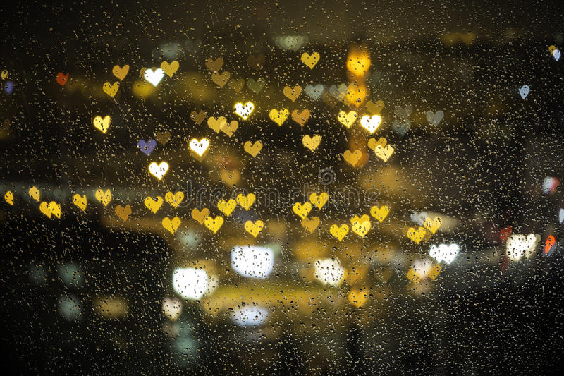 Small colorful hearth bokeh behind the wet glass for valentine day royalty free stock photography