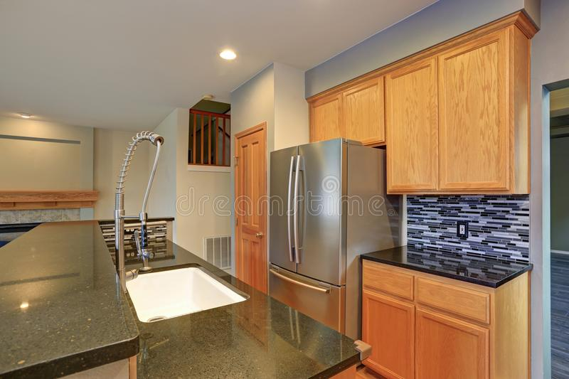 Small compact kitchen room with light wood cabinetry. Quartz counters and mosaic backsplash stock images