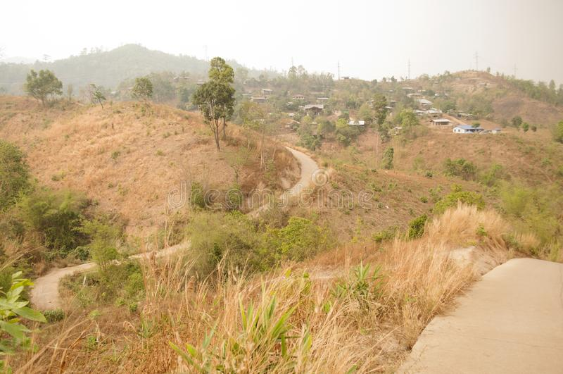 Small concrete road winding on tiny dry hills leading to a tribal village in the North of Thailand during the tropical summer royalty free stock photography