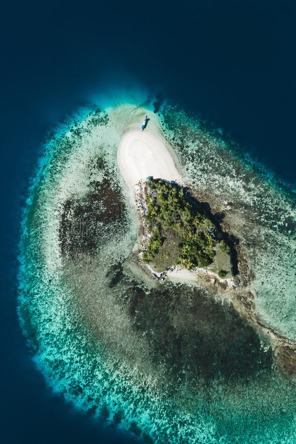 Small coral reef island with white sand beach. Aerial drone view. From above. Tropical background stock photos