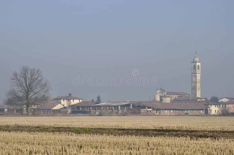 Small country village in winter, lombardy. Landscape with stubble fields and small agricultural village, shot in winter light on plains of lombardy royalty free stock image