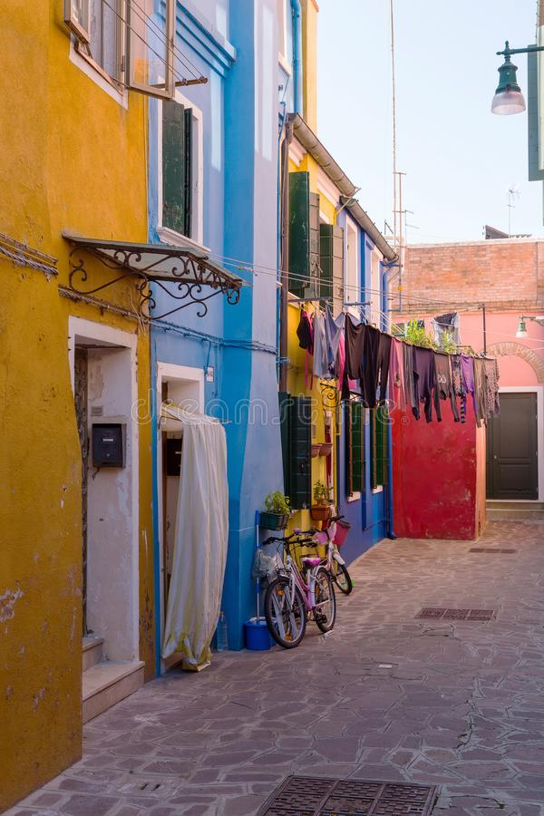 A small courtyard in Burano, with colored walls of houses and flowers royalty free stock images