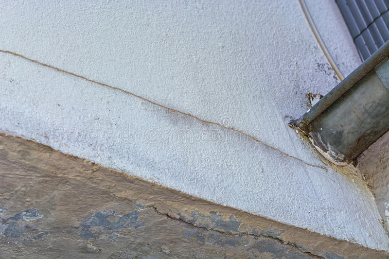 Small cracks in the plaster on the outside wall. Small cracks in the plaster on the outer wall caused by a tree bend stock photo