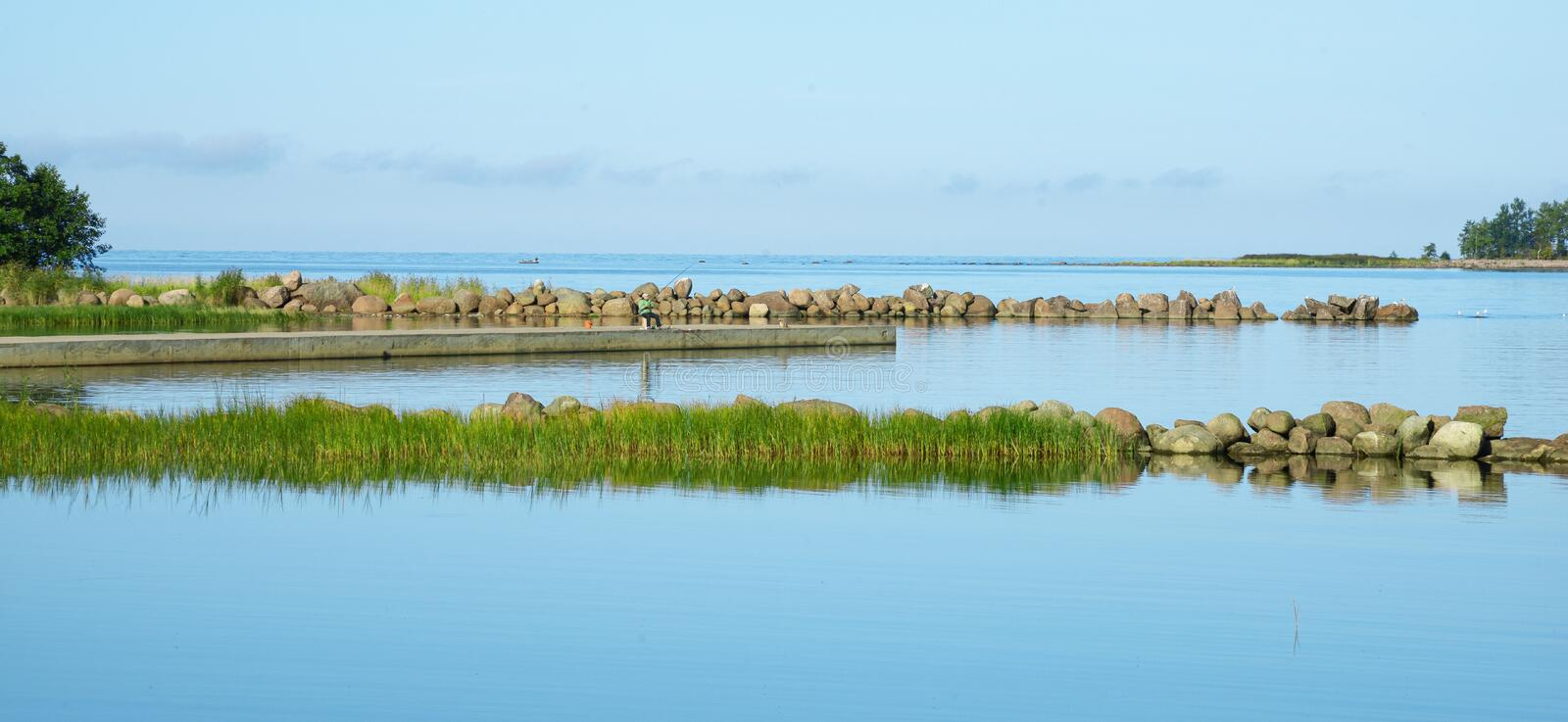 A small creek on the bay fenced with granite stones and grass. A clear summer morning. Blue water and clear sky stock photos