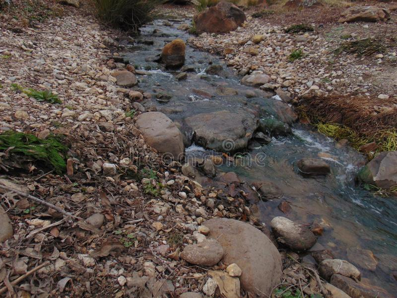 Small creek passing rocky riverbed stock image