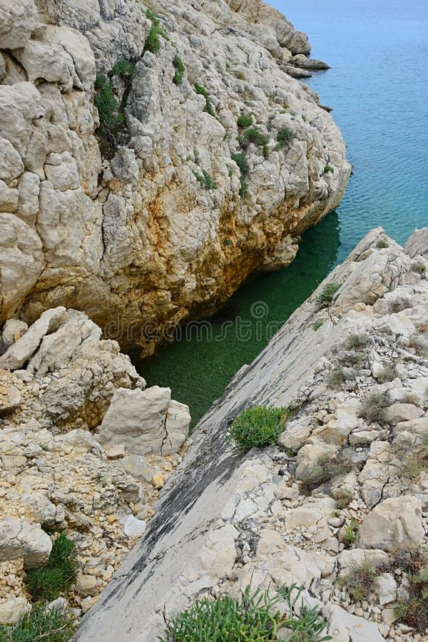 Small croatian shore cove hidden between steep cliffs with clear azure water and stony bottom, viewed from above. Afternoon sunlight stock photos