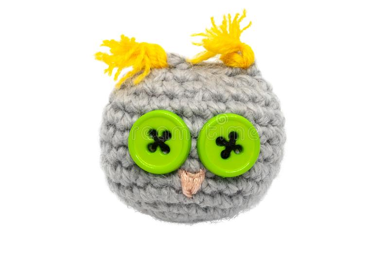 Small crocheted owl toy of gray threads with yellow ears, a pink nose and eyes of green buttons isolated on a white background. Small crocheted knitted owl toy stock photos