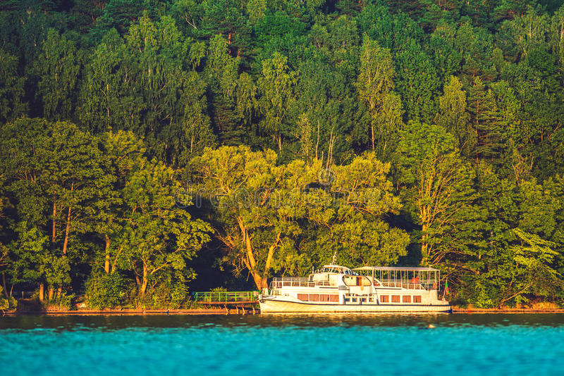 Small cruise ship in lake. Small cruise ship in blue water near green forest stock photography