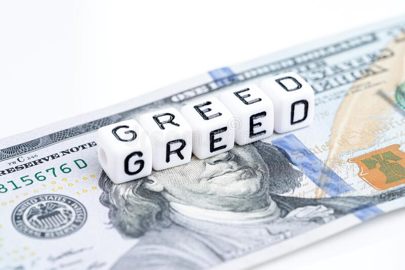 Small cube block with alphabets building the word Greed on US dollar banknote money on copy space white background using as greed. And fear in stock market or stock photography