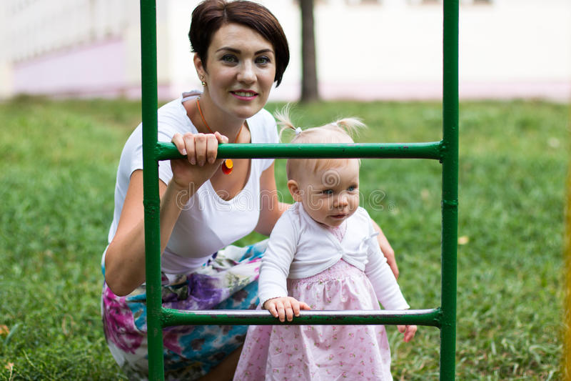 Small cute baby and nice mom. Outdoors royalty free stock images