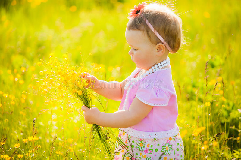 Small cute child playing alone in spring or summer sunny meadow stock photo