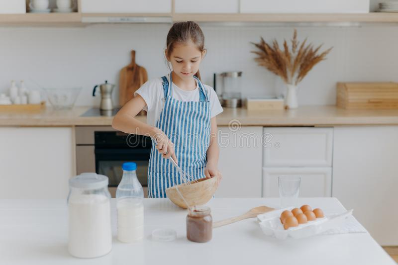 Small cute girl in apron, mixes ingredients, whisks with beater, uses eggs, milk, flour, tries new recipe, stands against kitchen stock image