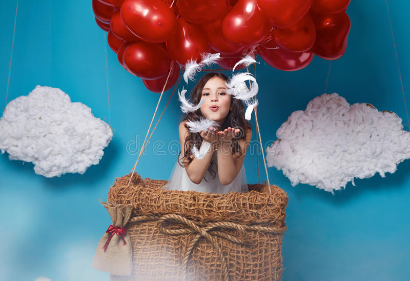 Small cute girl flying on red heart balloons Valentines day. Small cute girl with beautiful face on a board with a lot of red balloons having heart form on top royalty free stock photo
