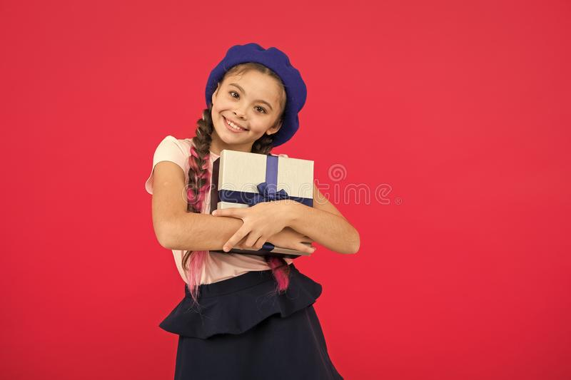 Small cute girl received gift pack with ribbon bow. Guess what your child dream about. Best toys and christmas gifts. Kid little girl in beret hat hold gift stock photos