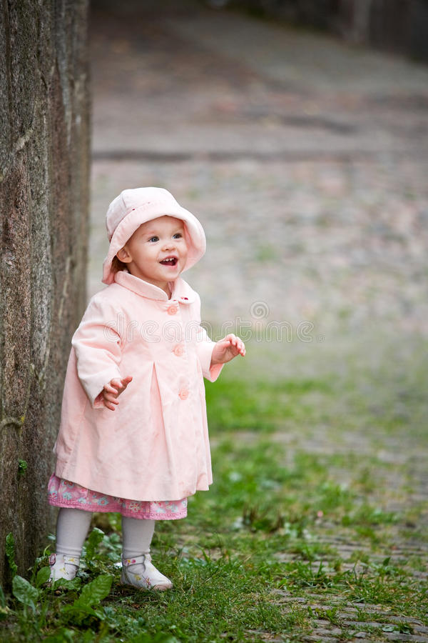 Small cute girl standing near old wall royalty free stock photo