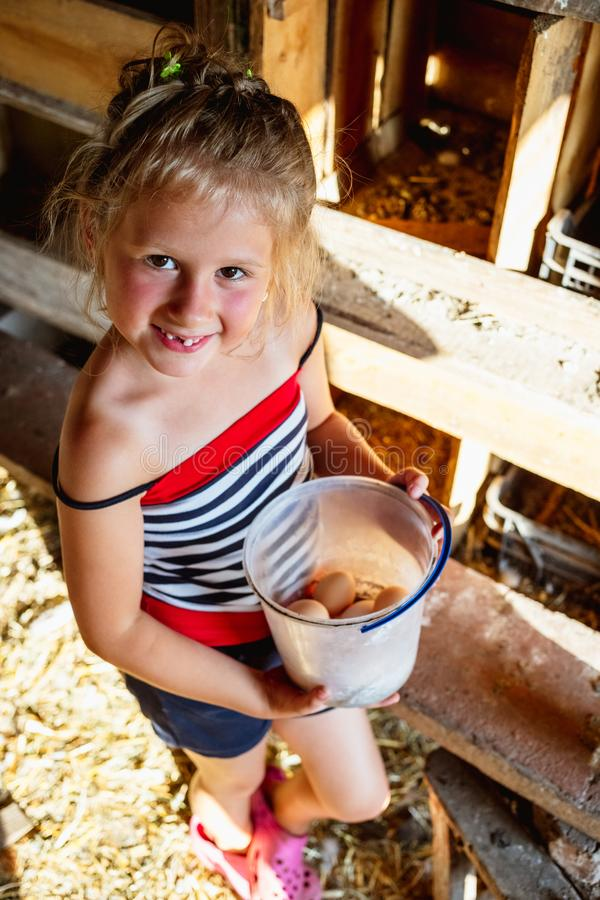 A small cute rural girl holding a plastic bucket with eggs. stock images
