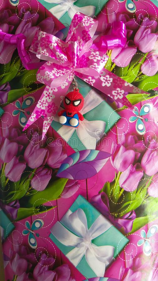 Cute gift wrap with Spiderman key chain toy on it. A small and cute Spiderman toy was taped with this gift pack for a little girl to be presented on her royalty free stock photos