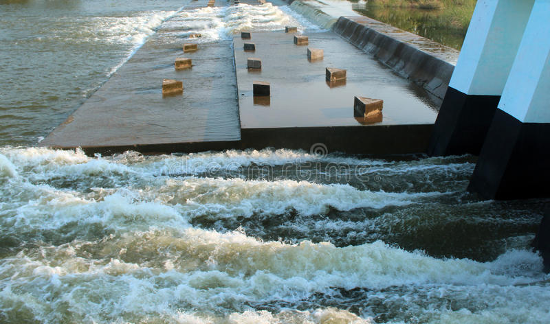 Small dam. Churning river water from opened shutter at a small dam royalty free stock photo