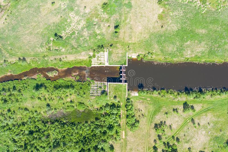 Small dam on a flat river flowing through green meadows, top aerial view.  stock photography