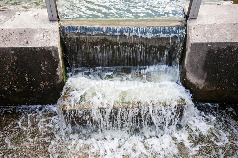 Small dam with flowing water and splashes outdoor. Selective royalty free stock photography