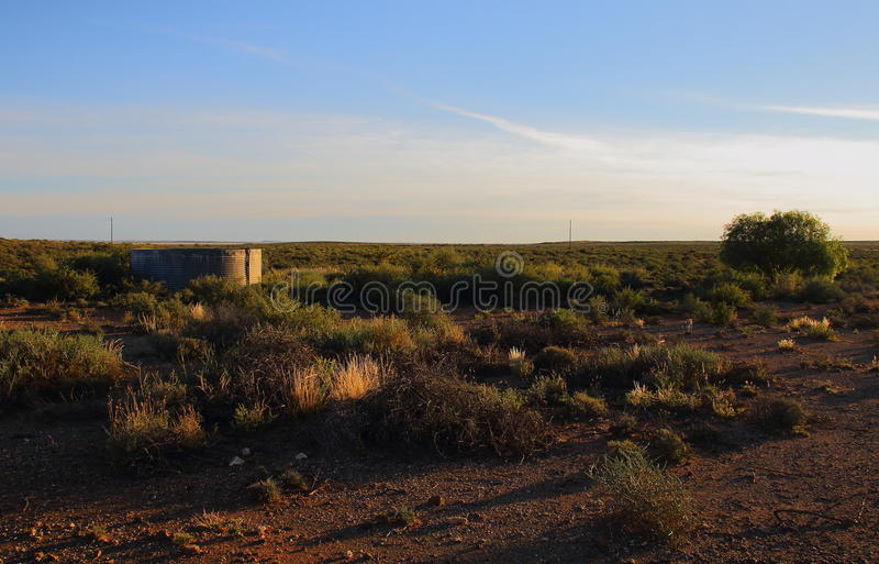 A small dam in the Karoo. A small farm dam in the sparse vegetation of the Great Karoo natural region in the Northern Cape of South Africa stock photos