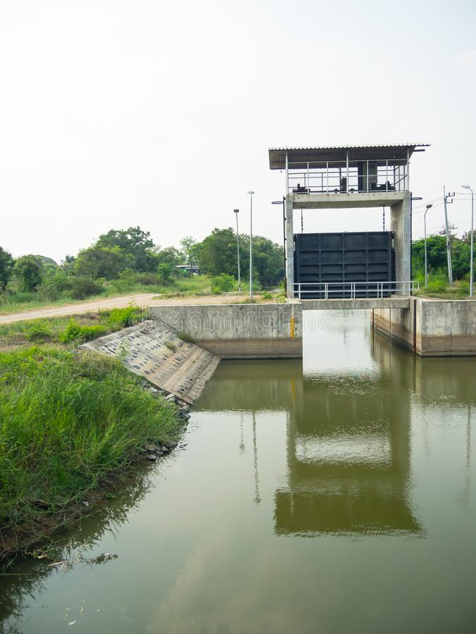 Small dam in a narrow canal in Thailand. Small dam is a barrier that stops or restricts the flow of water or underground streams in a narrow canal in Thailand royalty free stock image