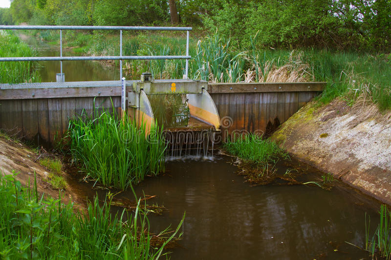 Small dam in a river. Small dam in a Dutch river in order to control the water level in a nature reserve royalty free stock photo