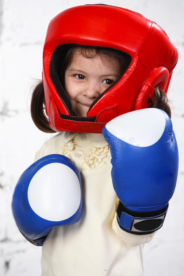 Small dark-haired girl in a protective helmet and stock photos
