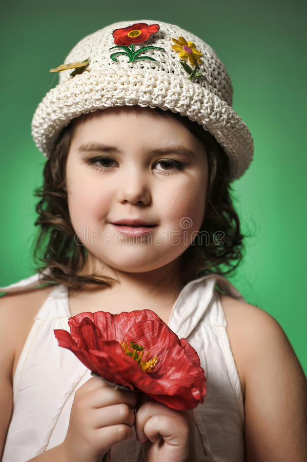 Small dark-haired girl with red poppy royalty free stock photography