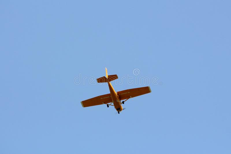 Small dark yellow plane used for panoramic flights flying high in air above local urban area. On clear blue sky background stock photos