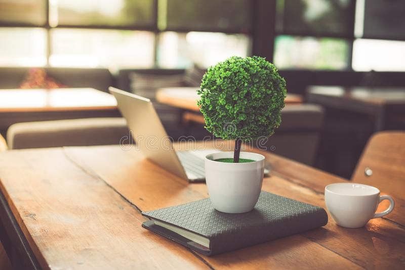 Small decorate tree, laptop, notebook and coffee cup in on wooden table in coffee shop. Relaxation and Business Co-working space stock images