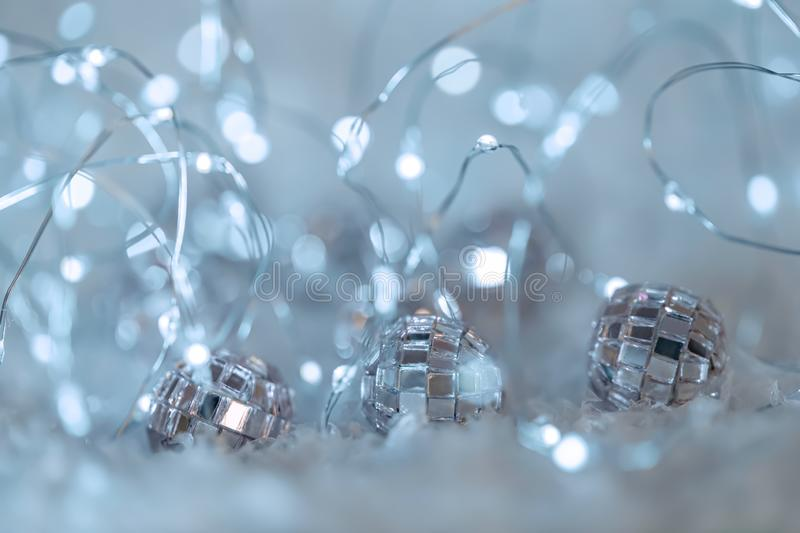 Small decorative balls with a mirror and a luminous garland on a snow. Blurred festive gray background with white bokeh. royalty free stock photos