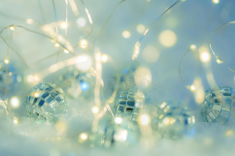 Small decorative balls with a mirror and a luminous garland on a snow. Blurred festive gray background with white bokeh. royalty free stock photo