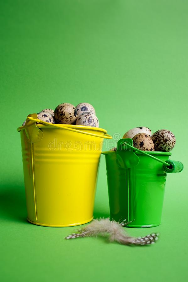 Small decorative buckets filled quail eggs on the green background stock photo