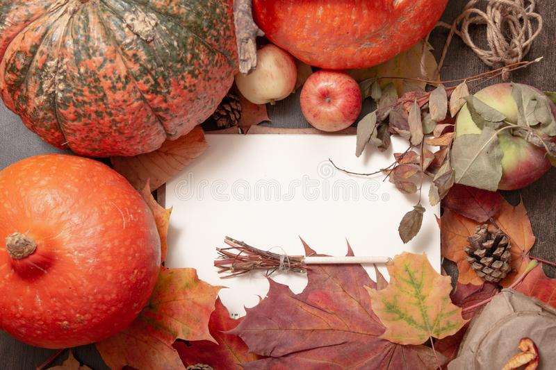 A small decorative witch's broom on a notepad, a cozy autumn still life with leaves, seasonal fruits. And vegetables, write down a recipe, top view, copy royalty free stock photography