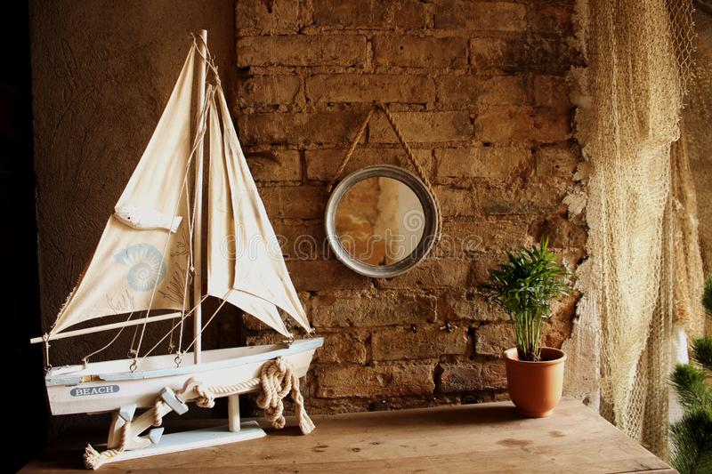 Small decorative yacht on table with potted plant and round mirror hanging on a red brick wall stock photography