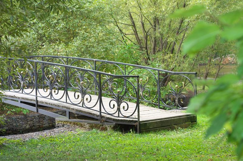 Small delicate wooden arched bridge over a quiet stream deep in the old, thick holiday Park. HD stock photo