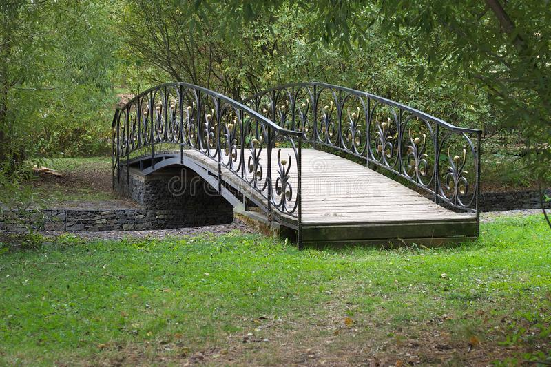 Small delicate wooden arched bridge over a quiet stream deep in the old, thick holiday Park. HD royalty free stock photos