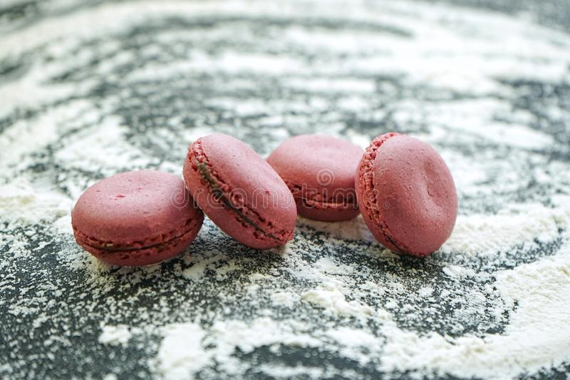 Small delicious purple macaroons on crumbly white wheat flour on black background. Small delicious purple macaroons crumbly white wheat flour black background stock photography