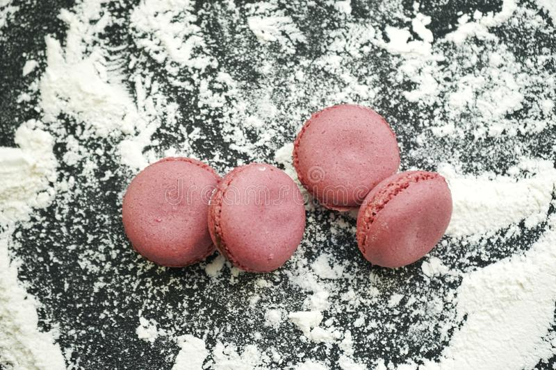 Small delicious purple macaroons on crumbly white wheat flour on black background. Small delicious purple macaroons crumbly white wheat flour black background stock images