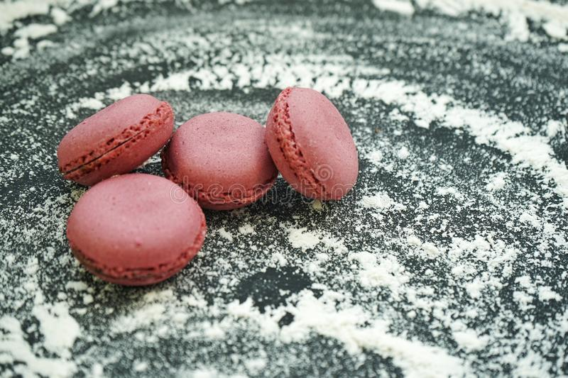 Small delicious purple macaroons on crumbly white wheat flour on black background. Small delicious purple macaroons crumbly white wheat flour black background royalty free stock photos