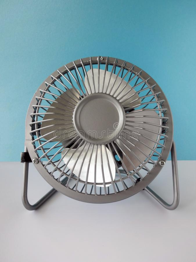 Small Desk Fan. Against a Blank Blue Background on a White Table royalty free stock images