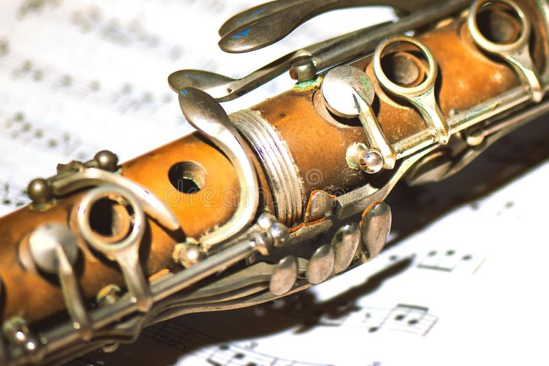 Small detail of an old clarinet on musical score.  royalty free stock photography