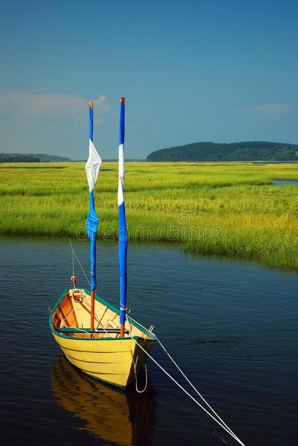 A small dinghy floats on the Essex River in Massachusetts. A small dinghy floats in a salt marsh on the Essex River in Massachusetts stock photos