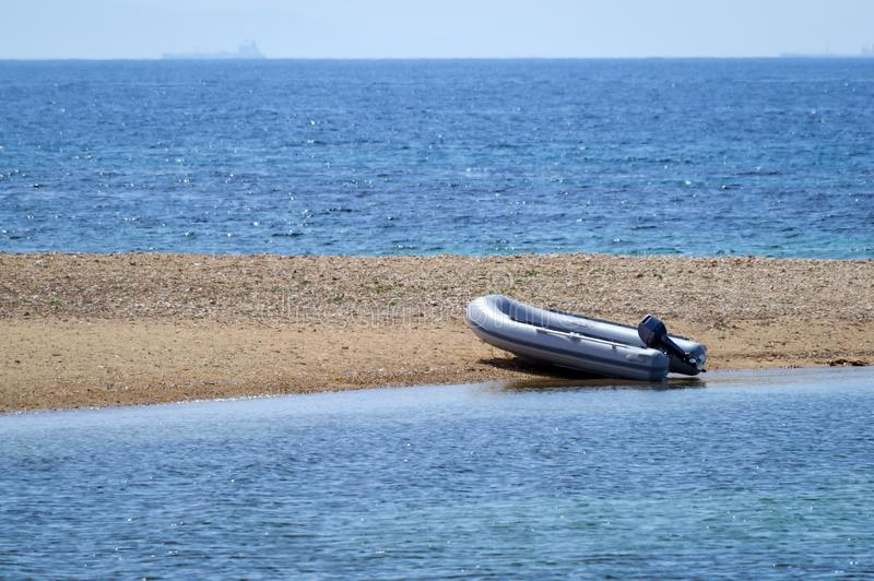 Small dinghy at a lonely beach. View of a small dinghy at a lonely beach with clear blue waters, Aegean - Greece stock photos