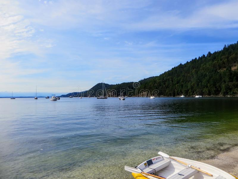A small dinghy sitting long the beaches of an island with beautiful clear water in the background and many boats anchored. In the bay, on Galiano Island stock photography