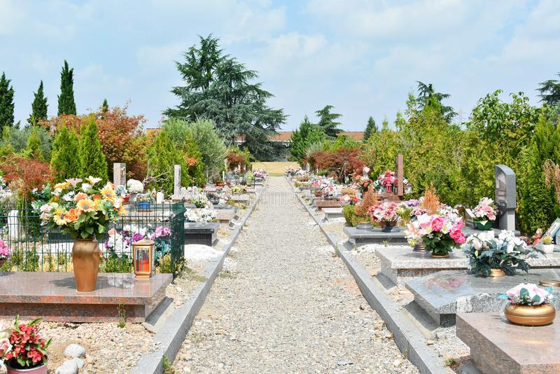 Small dirt path with side graves in the cemetery. Sequence of tombs with colored plastic flowers on the ground stock photos