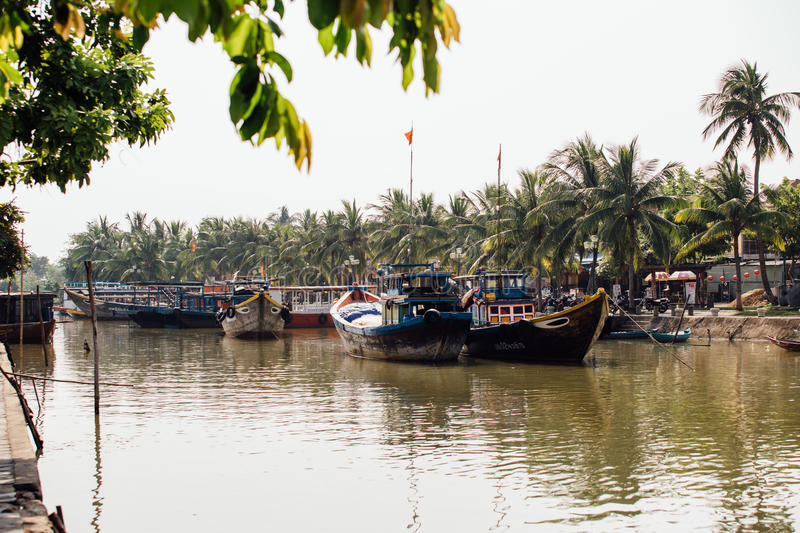 Small dirty river with boats and bridges in Asia stock images