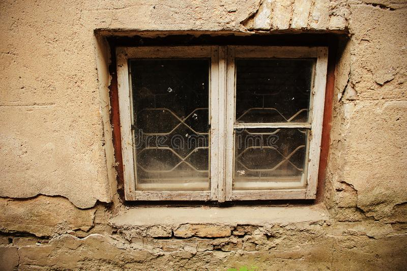 Small dirty window in old gray plaster wall royalty free stock photo